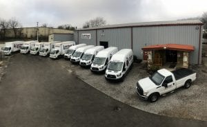 Wide view of Lift Truck Service fleet of trucks and vans parked outside in front of office