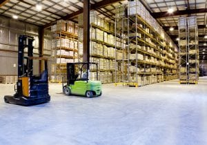 Large modern warehouse with forklifts in ready position
