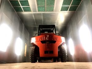 Low Angle Red Nissan Forklift Parked in Paint Booth