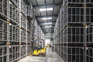 Forklift retrieving tire pallet from top of four level stack
