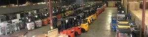 Warehouse full of Forklifts parked beside each other. Sales, Rentals, and Service