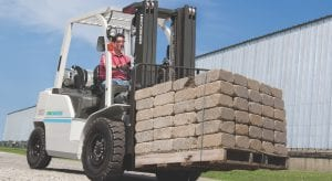 IniCarriers Forklift moving block outside with a smiling driver in a red shirt
